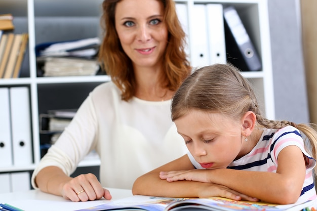 Blond little reading together with mom
