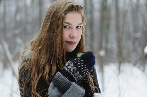 A blond long-haired girl is drinking coffee on a winter day outside