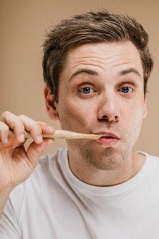 Blond man brushing his teeth with a wooden toothbrush