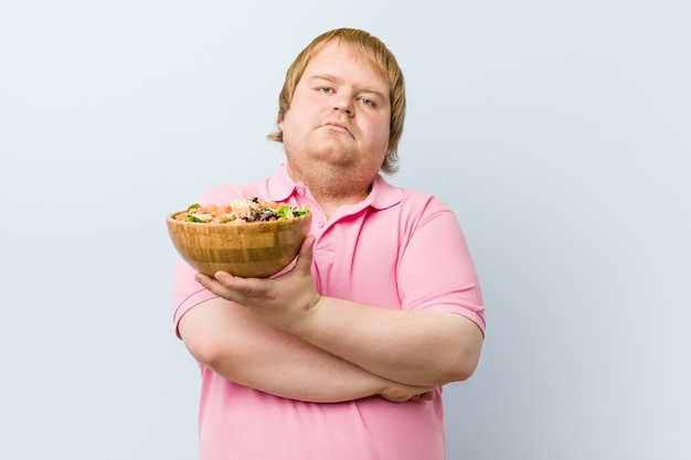Blond man holding a salad bowl