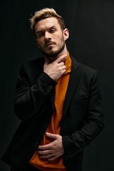 Блондинка держит руку на шее и оранжевом свитере, черная модель куртки