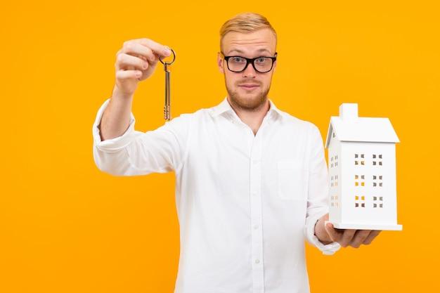 白いシャツを着た金髪の男が黄色の壁にアパートの建物の紙モデルとキーを保持しています。
