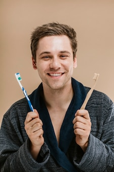 Blond man in a robe choosing between a wooden toothbrush and a plastic one