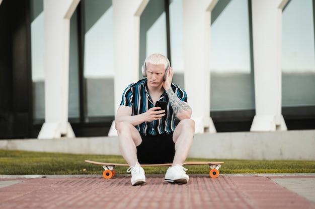 路上でヘッドフォンで音楽を聴きながらスケートボードに座っている金髪の男
