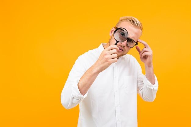 Блондинка в классической белой рубашке в очках смотрит через лупу на желтый