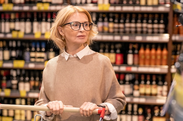 Blond mature female customer in casualwear pushing shopping cart while walking along shelves with drinks in supermarket