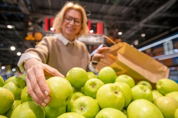 Блондинка зрелая женщина-покупательница с бумажным пакетом выбирает свежие зеленые яблоки на фруктовой витрине, посещая супермаркет и покупая еду