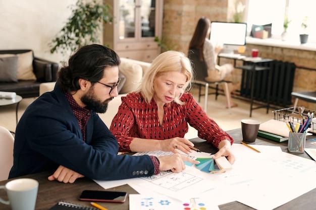Зрелая блондинка-дизайнер и ее бородатый коллега-мужчина указывают на цветовую палитру, работая над новым творческим проектом в офисе