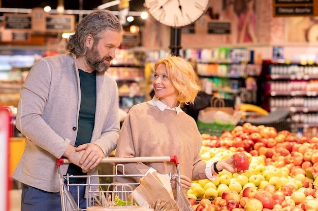 Блондинка зрелая женщина держит красное яблоко и смотрит на своего мужа с тележкой для покупок, одновременно выбирая фрукты в супермаркете