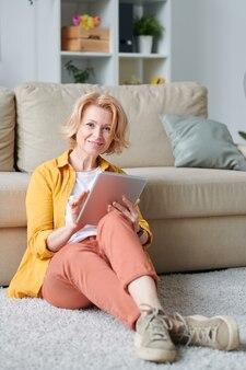 ソファで床に座って、家庭環境でオンラインビデオを見ながらタブレットを使用してカジュアルウェアの金髪成熟した女性