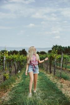 田舎を歩くデニムショートパンツとノースリーブシャツでスリムな完璧なボディのブロンドモデルの女の子。夏の旅行