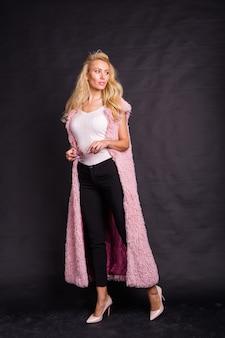 暗い背景の上にポーズをとってピンクのカーディガンの金髪モデル