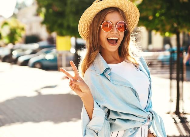 Белокурая модель в летней одежде позирует на улице, показывая знак мира