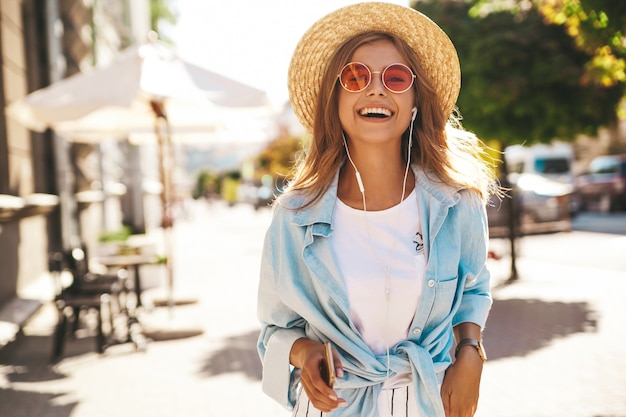 Blond model in summer clothes posing on the street