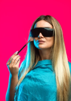 검은 선글라스를 착용하고 화장품을 적용하는 금발 모델