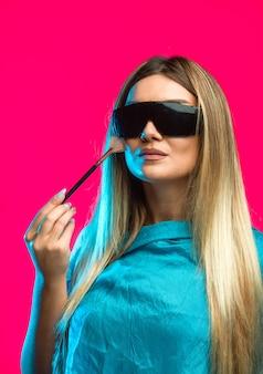 Modello biondo che indossa occhiali da sole neri e applica cosmetici.