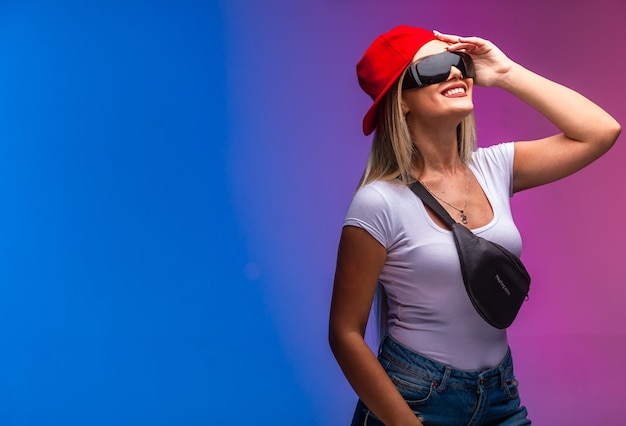 Blond model wearing sport outfits and sunglasses looking up.