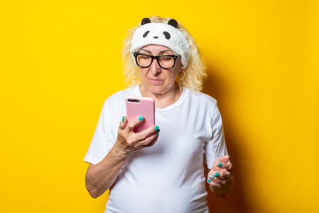 Blond old woman in glasses and sleep mask looking at phone