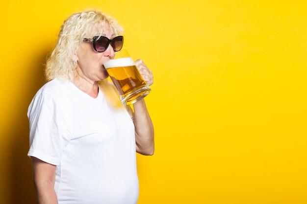 Блондинка старушка в белой футболке, в солнцезащитных очках пьет пиво