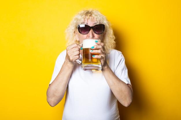 맥주 한 잔을 들고 선글라스와 흰색 티셔츠에 금발 늙은 여자