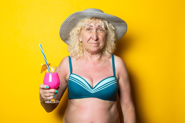 Blond old woman in a swimsuit holds a cocktail on a yellow surface
