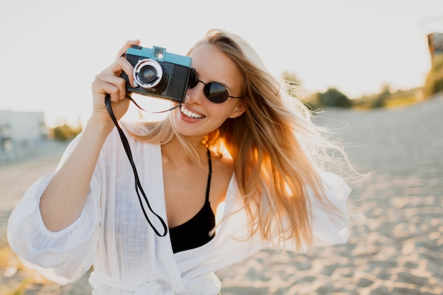 Bionda donna allegra che tiene la retro macchina fotografica e divertirsi sulla calda spiaggia assolata. vacanze estive e concetto di viaggio. bellezze naturali, vacanze in asia. occhiali da sole alla moda, vestito bianco.