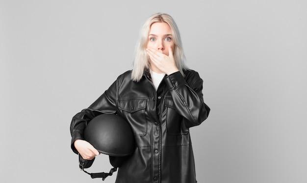 Блондинка красивая женщина закрыла рот руками с потрясенным. концепция мотоциклистов