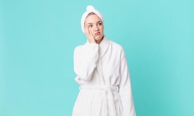 Блондинка красивая женщина чувствует скуку, разочарование и сонливость после утомительного и ношения халата