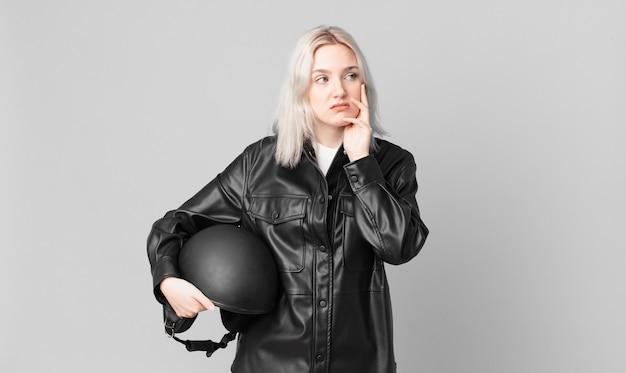 Блондинка симпатичная женщина чувствует себя скучающей, разочарованной и сонной после утомительного. концепция мотоциклистов