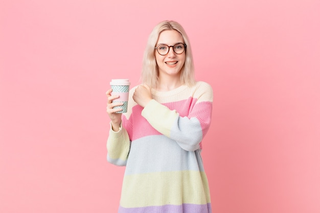Blond pretty woman feeling happy and facing a challenge or celebrating. coffee concept