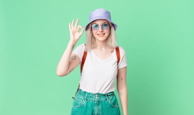 幸せを感じている金髪のきれいな女性は、大丈夫なジェスチャーで承認を示しています。夏のコンセプト