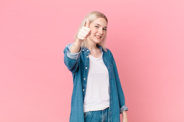 Блондинка красивая женщина чувствует себя гордой, позитивно улыбаясь с большими пальцами руки вверх