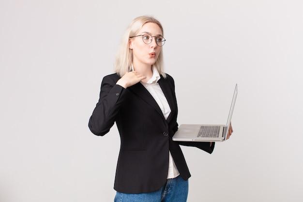 Блондинка красивая женщина чувствует стресс, тревогу, усталость и разочарование и держит ноутбук