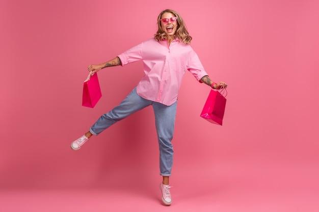 Блондинка красивая женщина в розовой рубашке и джинсах, улыбаясь, прыгает на розовом фоне, изолирована, весело держа сумки для покупок