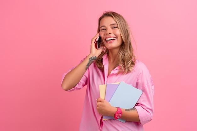 분홍색 셔츠를 입은 금발의 예쁜 여성이 노트북을 들고 웃고 분홍색으로 포즈를 취하는 스마트폰을 사용합니다.