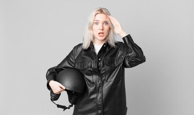 Блондинка красивая женщина выглядит счастливой, удивленной и удивленной. концепция мотоциклистов