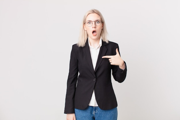 Blond pretty woman looking shocked and surprised with mouth wide open, pointing to self. business concept
