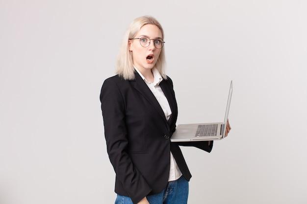 Блондинка красивая женщина выглядит очень шокированной или удивленной и держит ноутбук