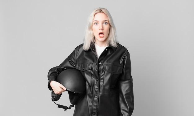 Блондинка красивая женщина выглядит очень шокированной или удивленной. концепция мотоциклистов