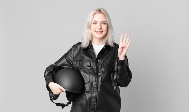 Блондинка красивая женщина улыбается и выглядит дружелюбно, показывая номер четыре. концепция мотоциклистов