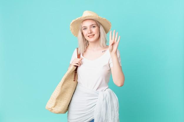 웃 고 친절 찾고 번호 4를 보여주는 금발 예쁜 여자. 여름 개념