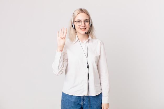 Блондинка красивая женщина улыбается и выглядит дружелюбно, показывая концепцию телемаркетинга номер четыре