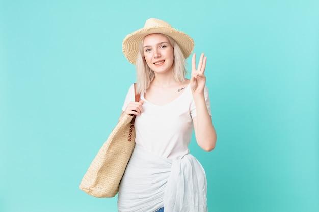 金髪のきれいな女性が笑顔でフレンドリーに見え、3番目を示しています。夏のコンセプト