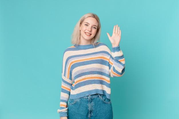 幸せに笑って、手を振って、あなたを歓迎し、挨拶する金髪のきれいな女性