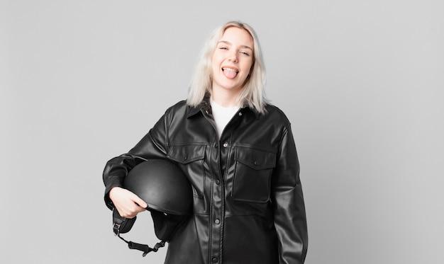 Блондинка симпатичная женщина с веселым и бунтарским отношением, шутит и высунула язык. концепция мотоциклистов