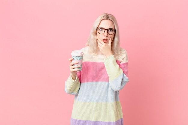 Блондинка красивая женщина с широко открытыми глазами и ртом и рукой за подбородок. концепция кофе