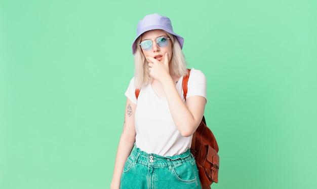 입과 눈을 크게 벌리고 턱에 손을 가진 아름 다운 금발 예쁜 여자. 여름 개념