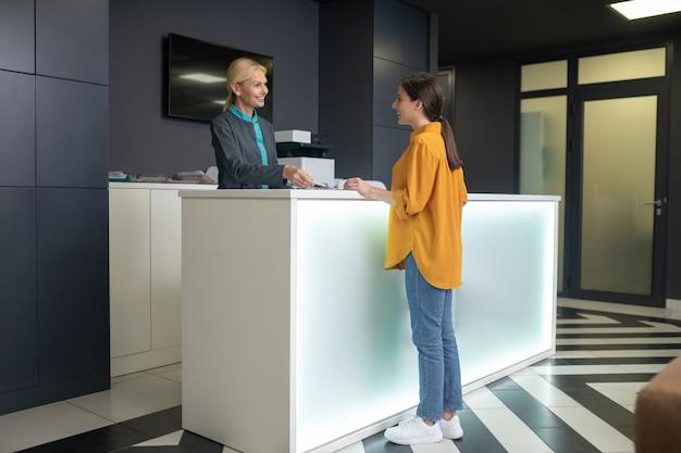 Блондинка в приемной в клинике приветствует новичка