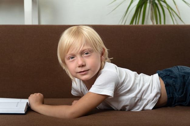金髪の男子生徒は本と一緒にソファに横たわっています。教科書を持つ少年の肖像画。