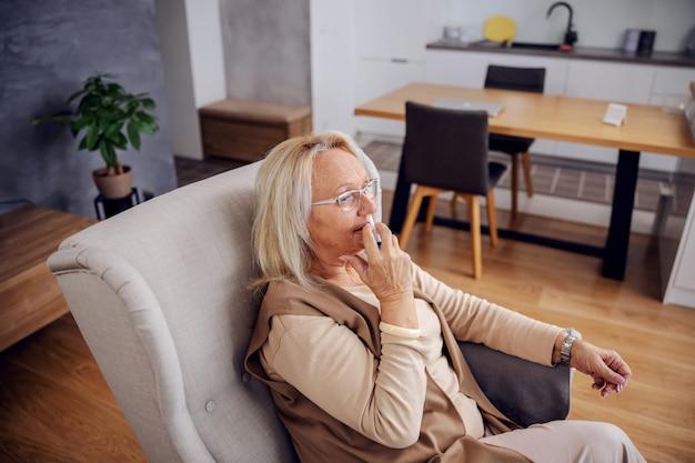Белокурая старшая женщина, сидящая в кресле у себя дома и распыляющая спрей для носа.